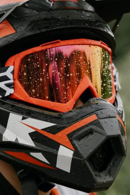 Picture shows orange dirt bike helmet googles up close.